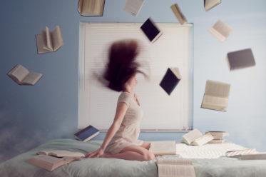 Symbolbild Frau auf Bett mit um sie herumfliegenden Büchern